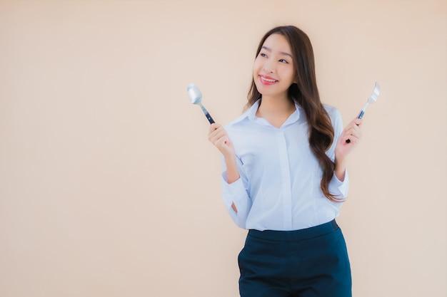 Portret mooie jonge aziatische bedrijfsvrouw met lepel en vork klaar te eten