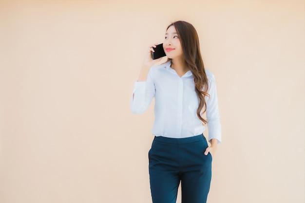 Portret mooie jonge aziatische bedrijfsvrouw met slimme mobiele telefoon en koffiekop
