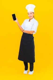 Portret mooie jonge aziatische chef-kok vrouw met slimme mobiele telefoon op gele geïsoleerde background
