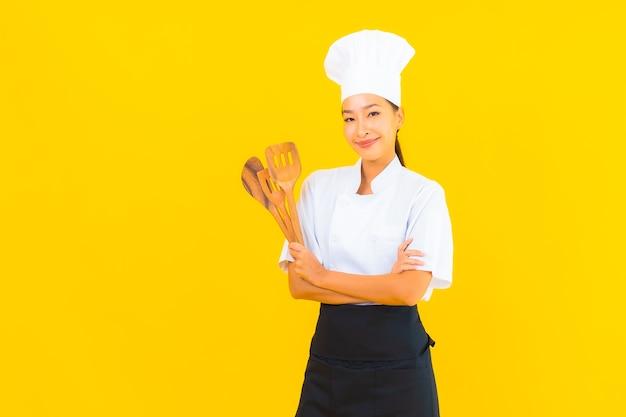 Portret mooie jonge aziatische chef-kok vrouw met spatel op gele geïsoleerde background