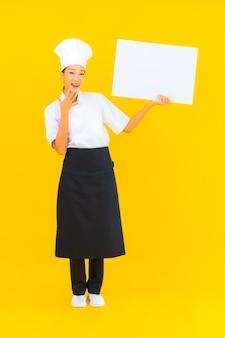 Portret mooie jonge aziatische chef-kok vrouw met wit leeg reclamebord op gele geïsoleerde background