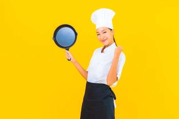 Portret mooie jonge aziatische chef-kok vrouw met zwarte pan op gele geïsoleerde background