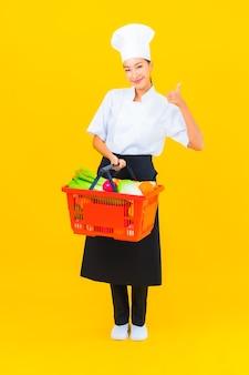 Portret mooie jonge aziatische chef-kokvrouw met kruidenierswinkelmand van supermarkt op gele geïsoleerde background