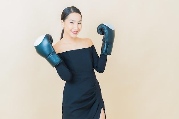 Portret mooie jonge aziatische vrouw boksen met handschoen op geel