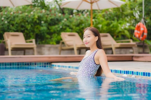 Portret mooie jonge aziatische vrouw buiten ontspannen in zwembad in vakantiereis