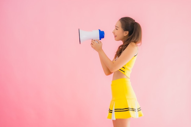 Portret mooie jonge aziatische vrouw cheerleader met megafoon
