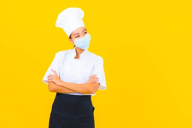 Portret mooie jonge aziatische vrouw chef-kok draagt een masker ter bescherming van covid19 of coronavirus op gele geïsoleerde achtergrond