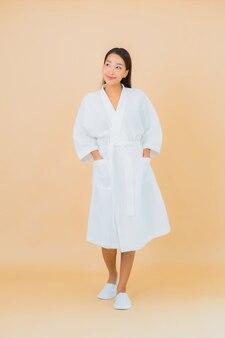 Portret mooie jonge aziatische vrouw die badjas met glimlach op beige draagt
