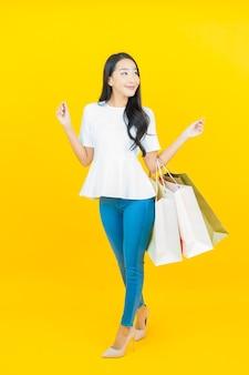 Portret mooie jonge aziatische vrouw die lacht met boodschappentas op geel