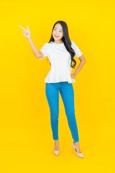 Portret mooie jonge aziatische vrouw die lacht op geel