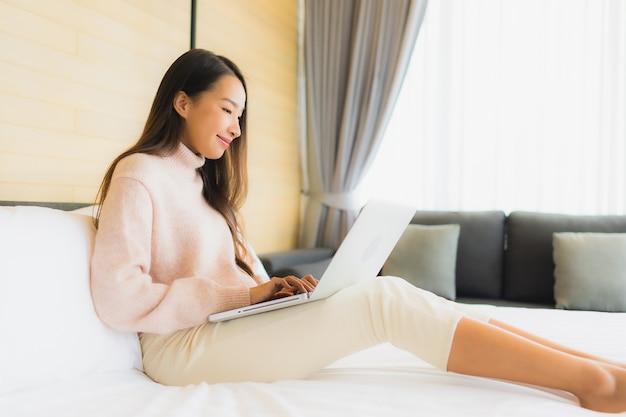 Portret mooie jonge aziatische vrouw die laptop met mobiele telefoon op bed met behulp van