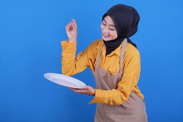 Portret mooie jonge aziatische vrouw die lege schotel op blauwe muur toevoegt
