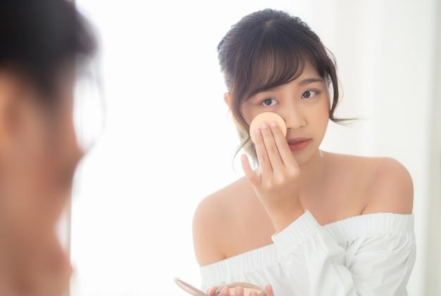 Portret mooie jonge aziatische vrouw die poederdonsje toepassen bij wangmake-up van schoonheidsmiddel