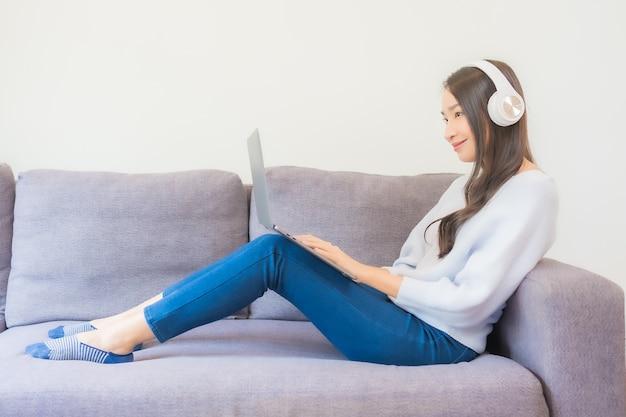Portret mooie jonge aziatische vrouw die slimme mobiele telefoon en hoofdtelefoon gebruikt om muziek in woonkamer te luisteren