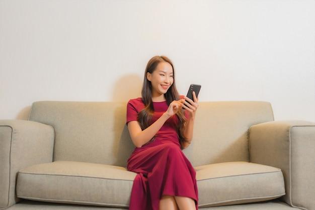 Portret mooie jonge aziatische vrouw die slimme mobiele telefoon op bank in woonkamerbinnenland met behulp van