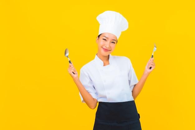 Portret mooie jonge aziatische vrouw draagt chef-kok of kookuniform met lepel en vork op gele geïsoleerde achtergrond