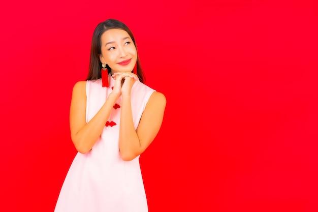Portret mooie jonge aziatische vrouw draagt chinees nieuwjaarskleding op rode muur