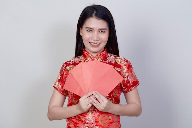 Portret mooie jonge aziatische vrouw draagt ?? een chinese jurk met rode pakket monetaire geschenk van felicitatie groet gelukkig nieuw jaar 2021 geïsoleerd op lichtgrijze achtergrond met kopie ruimte