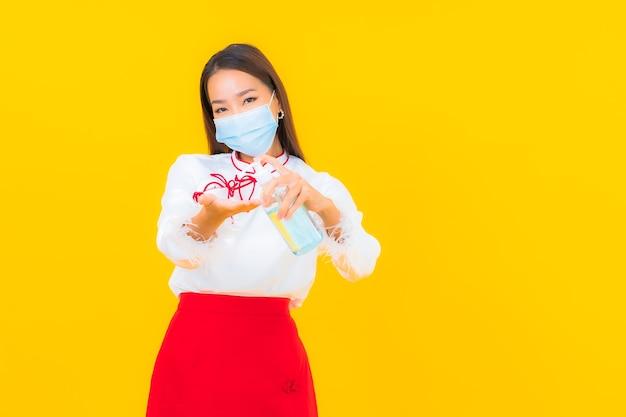 Portret mooie jonge aziatische vrouw draagt een masker en gebruikt alcoholgel om covid19 op geel te beschermen