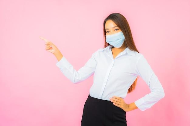 Portret mooie jonge aziatische vrouw draagt een masker ter bescherming tegen covid19 en coronavirus op roze muur