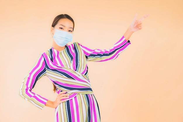 Portret mooie jonge aziatische vrouw draagt ?? masker voor bescherming van het coronavirus of covid19 op kleur
