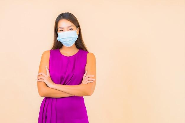 Portret mooie jonge aziatische vrouw dragen masker voor bescherming tegen covid19 of coronavirus op kleur achtergrond