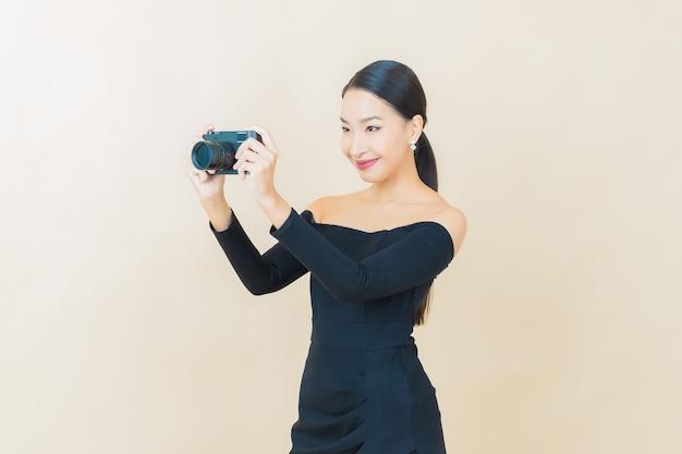 Portret mooie jonge aziatische vrouw gebruik camera op geel