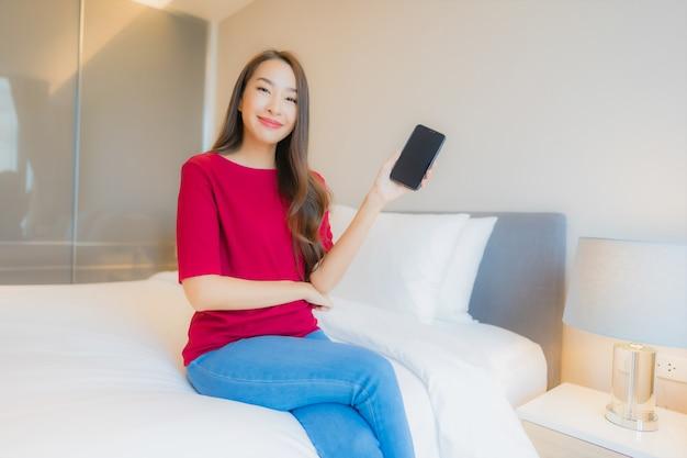 Portret mooie jonge aziatische vrouw gebruik slimme mobiele telefoon op bed