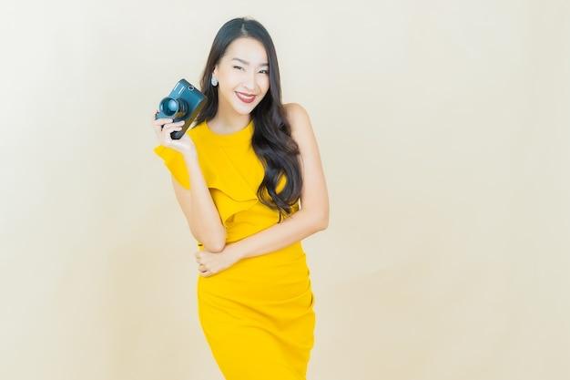 Portret mooie jonge aziatische vrouw gebruikt camera op beige muur