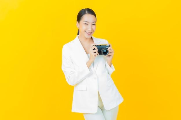 Portret mooie jonge aziatische vrouw gebruikt camera op kleurenmuur
