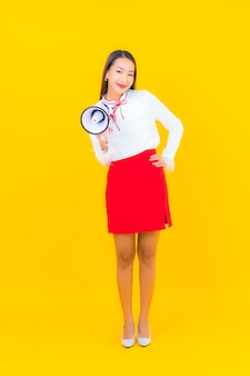 Portret mooie jonge aziatische vrouw gebruikt megafoon op geel
