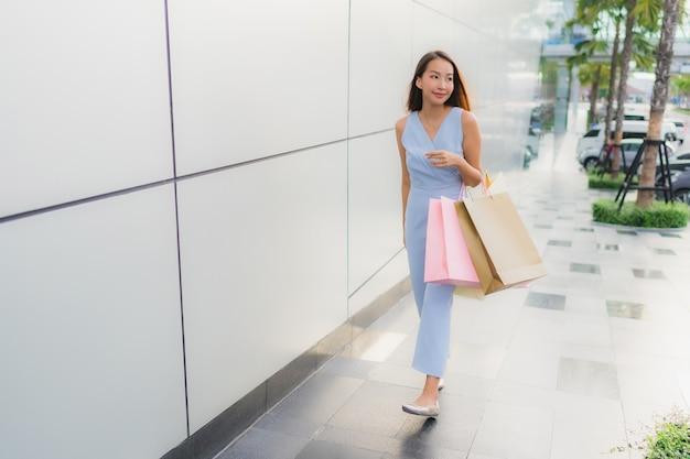 Portret mooie jonge aziatische vrouw gelukkig en glimlach met boodschappentas uit warenhuis