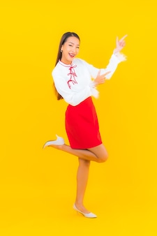 Portret mooie jonge aziatische vrouw glimlach in actie op geel on