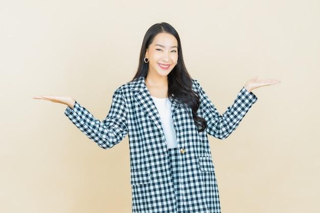 Portret mooie jonge aziatische vrouw glimlach met actie op beige
