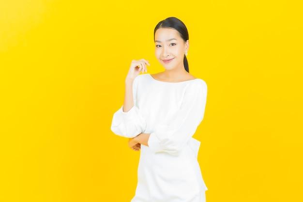 Portret mooie jonge aziatische vrouw glimlach met actie op geel with
