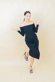 Portret mooie jonge aziatische vrouw glimlach met actie op geel