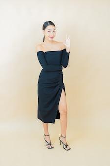 Portret mooie jonge aziatische vrouw glimlach met actie op geel Gratis Foto