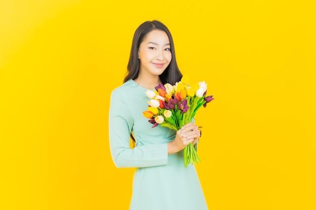 Portret mooie jonge aziatische vrouw glimlach met bloem op geel with