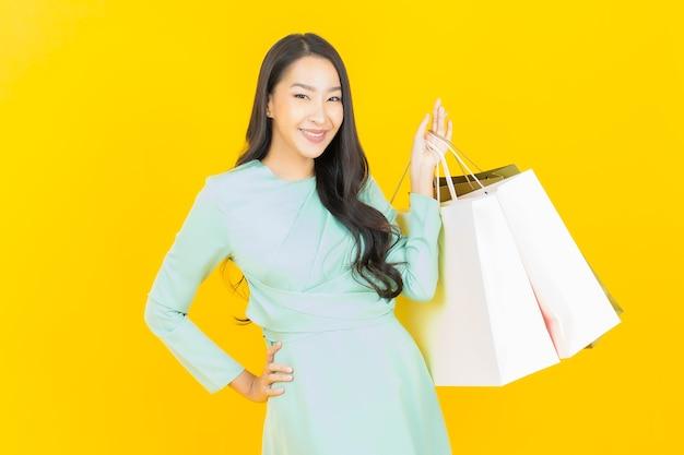 Portret mooie jonge aziatische vrouw glimlach met boodschappentas op geel on