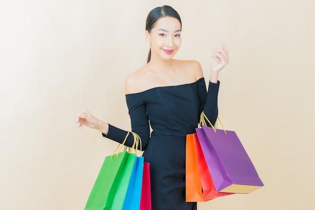 Portret mooie jonge aziatische vrouw glimlach met boodschappentas op geel