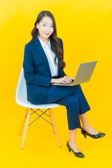 Portret mooie jonge aziatische vrouw glimlach met computer laptop op geel