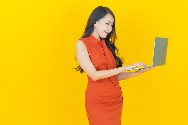Portret mooie jonge aziatische vrouw glimlach met computer laptop op geïsoleerde achtergrond