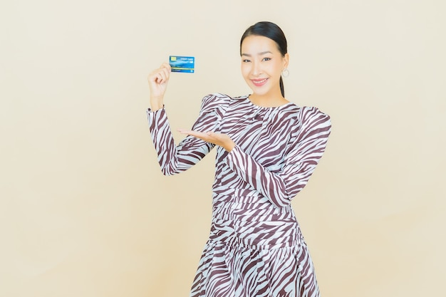 Portret mooie jonge aziatische vrouw glimlach met creditcard op beige with