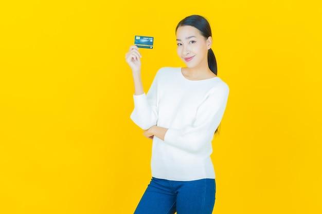 Portret mooie jonge aziatische vrouw glimlach met creditcard op geel