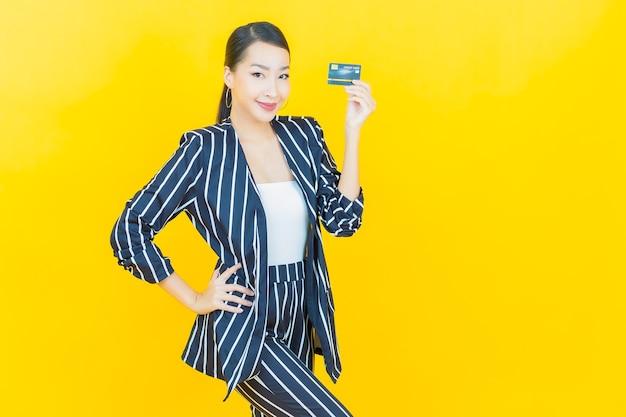 Portret mooie jonge aziatische vrouw glimlach met creditcard op kleur achtergrond