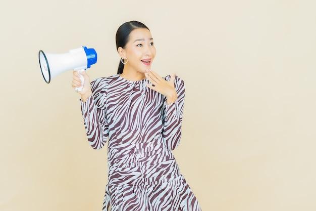 Portret mooie jonge aziatische vrouw glimlach met megafoon op beige