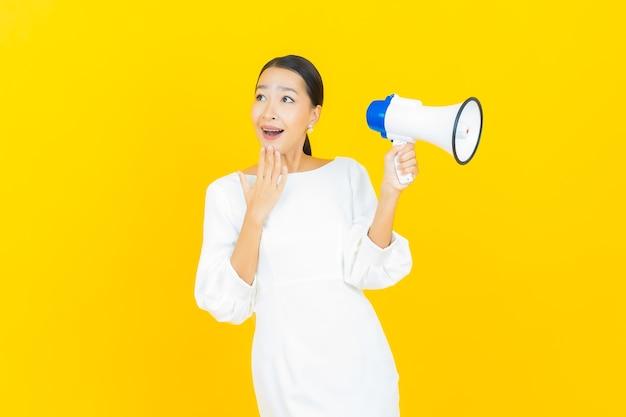 Portret mooie jonge aziatische vrouw glimlach met megafoon op geel mega