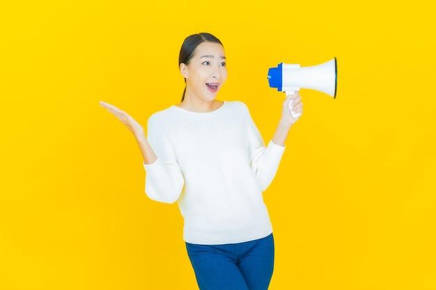 Portret mooie jonge aziatische vrouw glimlach met megafoon op geel
