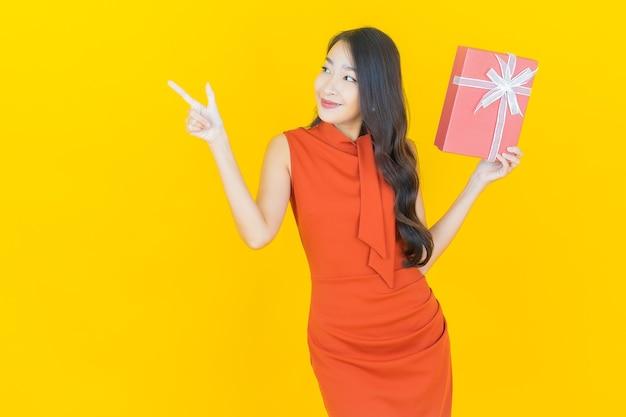 Portret mooie jonge aziatische vrouw glimlach met rode geschenkdoos op geel