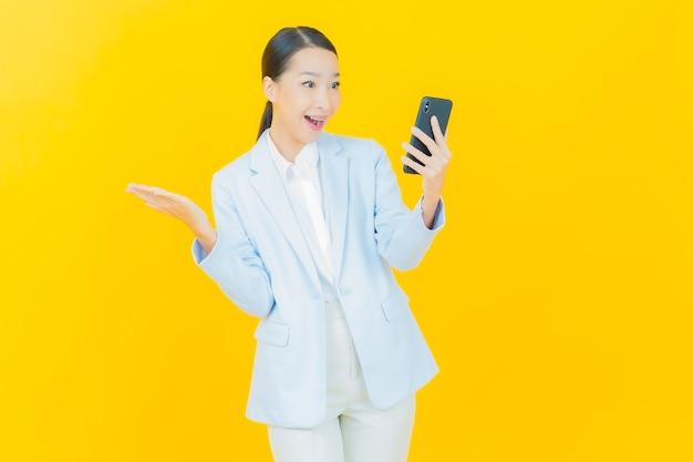 Portret mooie jonge aziatische vrouw glimlach met slimme mobiele telefoon op geel